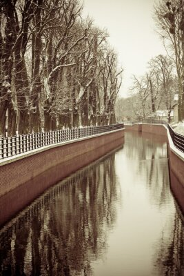 Wall mural  Park with river and embankment covered with snow
