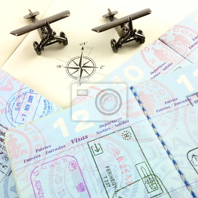 Passports, atlas compass rose and toy airplanes