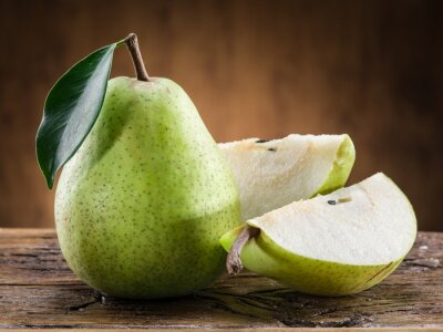 Wall mural Pear fruit with leaf on wooden background.