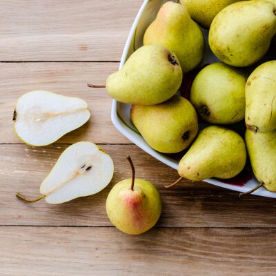 Wall mural pears in a bowl and pear halves on a wooden background