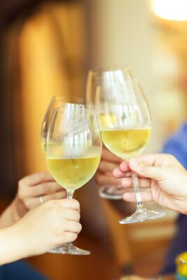 People cheering with white wine and rising glasses on celebration at restaurant