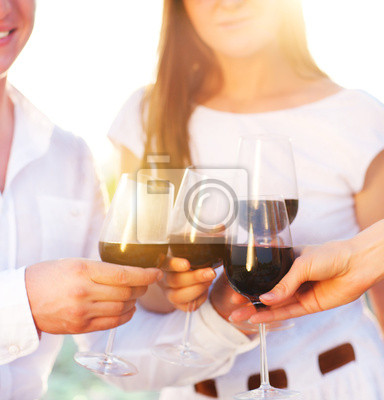 People holding glasses of red wine making a toast