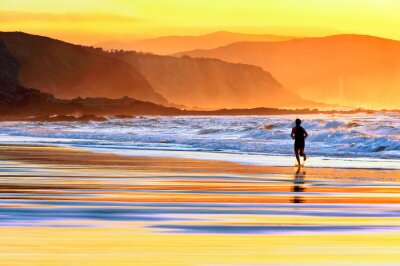 Wall mural person running on beach at sunset