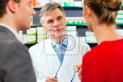 Pharmacist with customers in his pharmacy