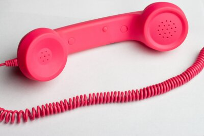 Wall mural Pink phone and cord on white surface