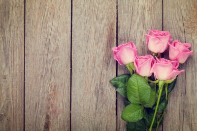 Wall mural Pink roses bouquet over wooden table