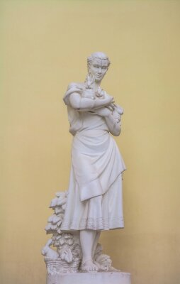 Plaster sculpture depicts  young woman with rabbits in her hands.