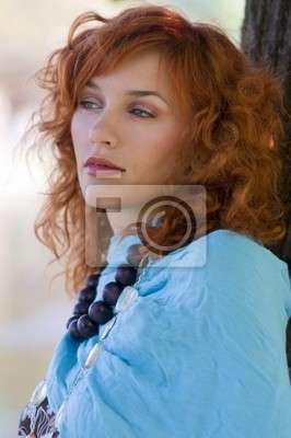portrait in the park of a red haired girl with a blue scarf