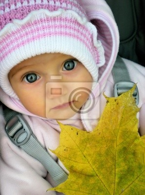Portrait of a little girl with big gray eyes with autumn leaf