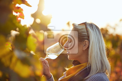 Wall mural Portrait of a woman tasting white wine in autumn colorful vineyard