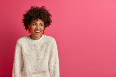 Wall mural Portrait of dreamy good looking woman with Afro hairstyle, looks away and laughs, discusses funny recent deal at work, has pleasant friendly talk, dressed in casual wear, isolated on pink wall