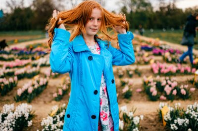 Portrait of strange red head girl in long blue coat and dress relaxes and thinks about something in the big flower garden