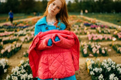 Portrait of strange red head girl in long blue coat and pink warm jacket relaxes and thinks about something in the big flower garden.