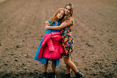 Portrait of strange red head girl in long blue coat and pink warm jacket relaxes and thinks about something on the big empty field with her elder sister in long dark dress