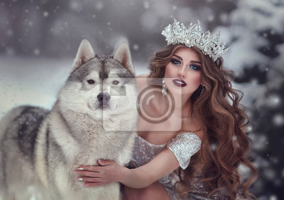 Wall mural Portrait of woman in silver dress and crown as snow Queen, in winter forest with Husky dog .The fairy Princess and the wolf in the winter.