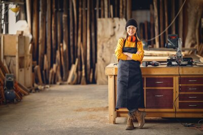 Wall mural Positive woman working in joinery workshop