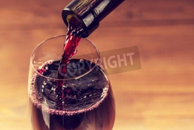Wall mural Pouring red wine into the glass against wooden background