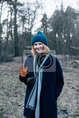 Pretty and cute beautiful red head girl with freckles, in big blue hat, with scarf and coat, stands in middle of forest, picks up fallen leaves and smiles. vertical photo mobile adapted