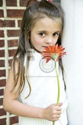Pretty little girl standing by a column holding a flower.