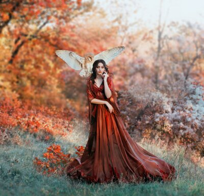 Wall mural pretty young girl with black hair in cold forest, orange foliage of trees, fairy of autumn season in long red burgundy vintage dress with chic train, lady with white owl on shoulder, bloody sorceress