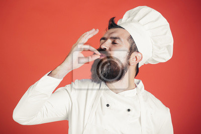 Wall mural Professional chef man showing sign for delicious. Male chef in white uniform with perfect sign. Serious satisfied bearded chef, cook or baker gesturing excellent. Cook with taste approval gesture.