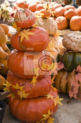 Pumpkins stacked 5 high garnished with a vine of fall leaves.