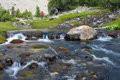 Wall mural Rapid and wide cascade river Fast moving water vivid rocky stones and group of people walking on green meadow on background