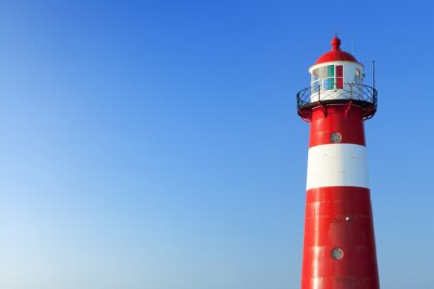 Wall mural Red and white lighthouse and a clear blue sky