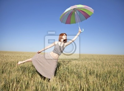 red-haired girl with umbrella at wheat field