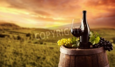 Wall mural Red wine bottle and glass on wooden keg. Vineyard on background