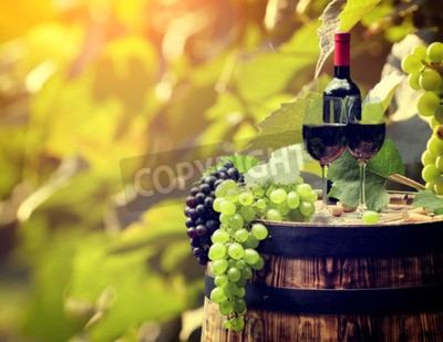 Wall mural Red wine bottle and wine glass on wodden barrel.