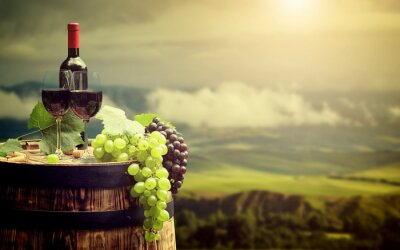 Wall mural Red wine bottle and wine glass on wodden barrel. Italy