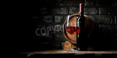 Wall mural Red wine on a background of old black bricks