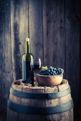 Wall mural Red wine with fresh grapes on old barrel