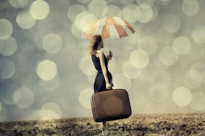 Wall mural Redhead girl with umbrella and suitcase at windy field