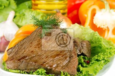 Roast beef on lettuce leaves with vegetables