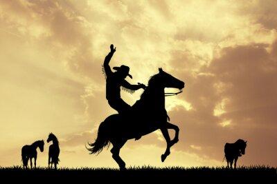 Wall mural Rodeo cowboy at sunset