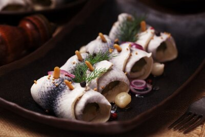 Wall mural Rolled herring in vinegar, served with onions and pickles.