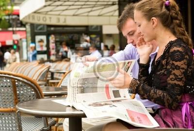 Romantic couple in Paris, reading newspaper in cafe