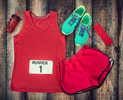 Wall mural Running gear laid out ready for race day, rustic wooden background