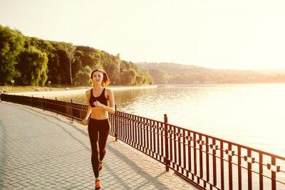 Wall mural Running woman. Runner jogging in sunny bright light. Female fitn