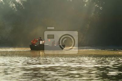 Rybacy zbierający sieci z połowem na rzece