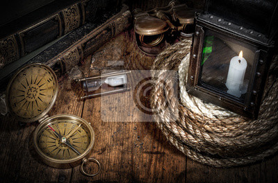 Scientific expedition and history background. Old book, compass, rope and vintage lamp on wood desk.