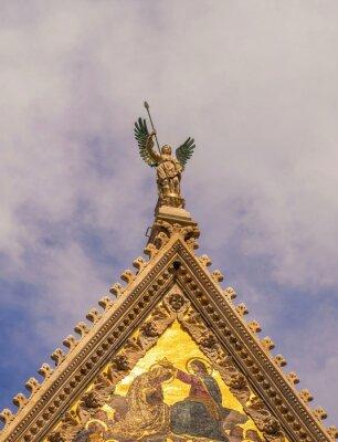 Sculptural figure of  Archangel on  roof of  basilica in  Italian city of Siena
