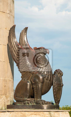 Sculpture-griffin monster with the shield in its paws