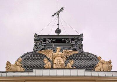 Sculptures of ancient gods adorn  pediment of an ancient building