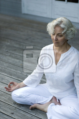 Senior doing yoga on the terrace