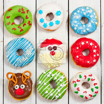 Set of Christmas donuts on light wooden background.