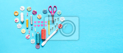 Wall mural sewing thread set of sewing supplies in knolling pattern on light blue background flat lay top view, template mockup hand made long banner