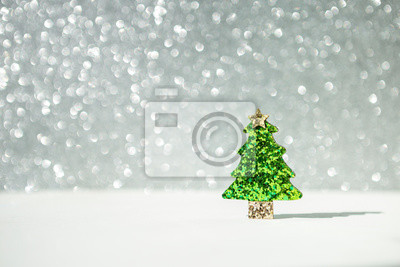 Wall mural Shiny green glitter Christmas tree over blurred shiny silver bokeh background, decorate item, shiny festive season and holiday